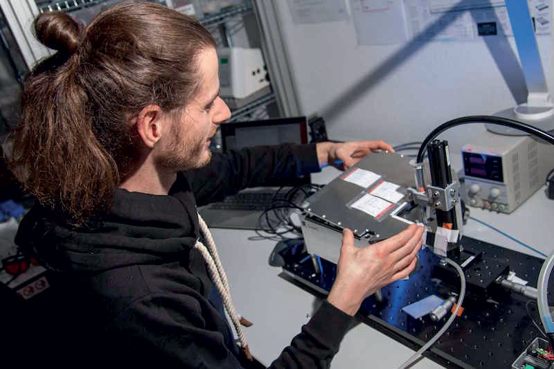 Q.ANT e SICK stanno sviluppando congiuntamente sensori quantistici per l'industria. Un dipendente di Q.ANT sta verificando la funzionalità complessiva del sensore su questo banco di misura.