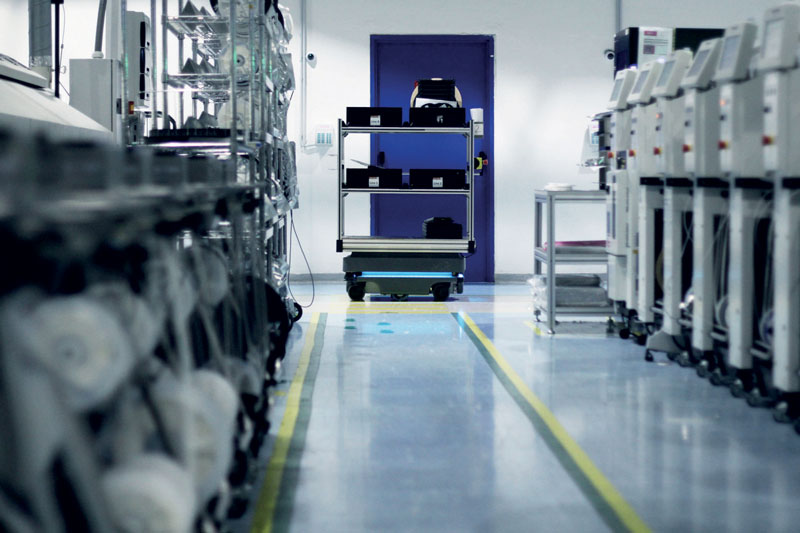 The mobile robots from MiR work autonomously around the manufacturing facility, open doors, move through a tunnel, bypass obstacles, stop and automatically recharge.