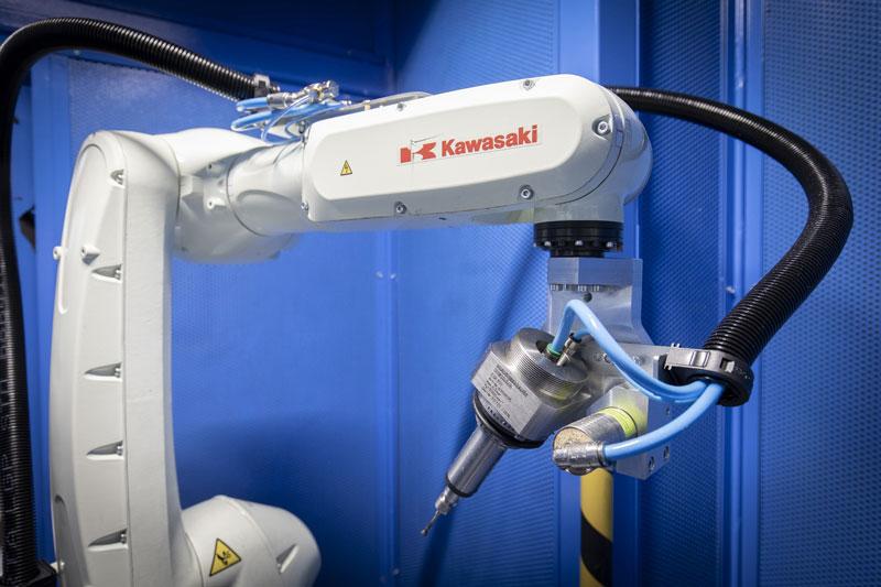 Nella prima cella due robot Kawasaki RS7L–F60, ognuno dotato di due turbine pneumatiche eseguono sia le sbavature nella parte interna del corpo, sia sulla parte esterna.